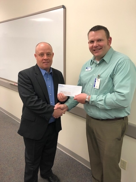 Been Eberwein presenting check to Michael Sutton for the Highland School District Foundation