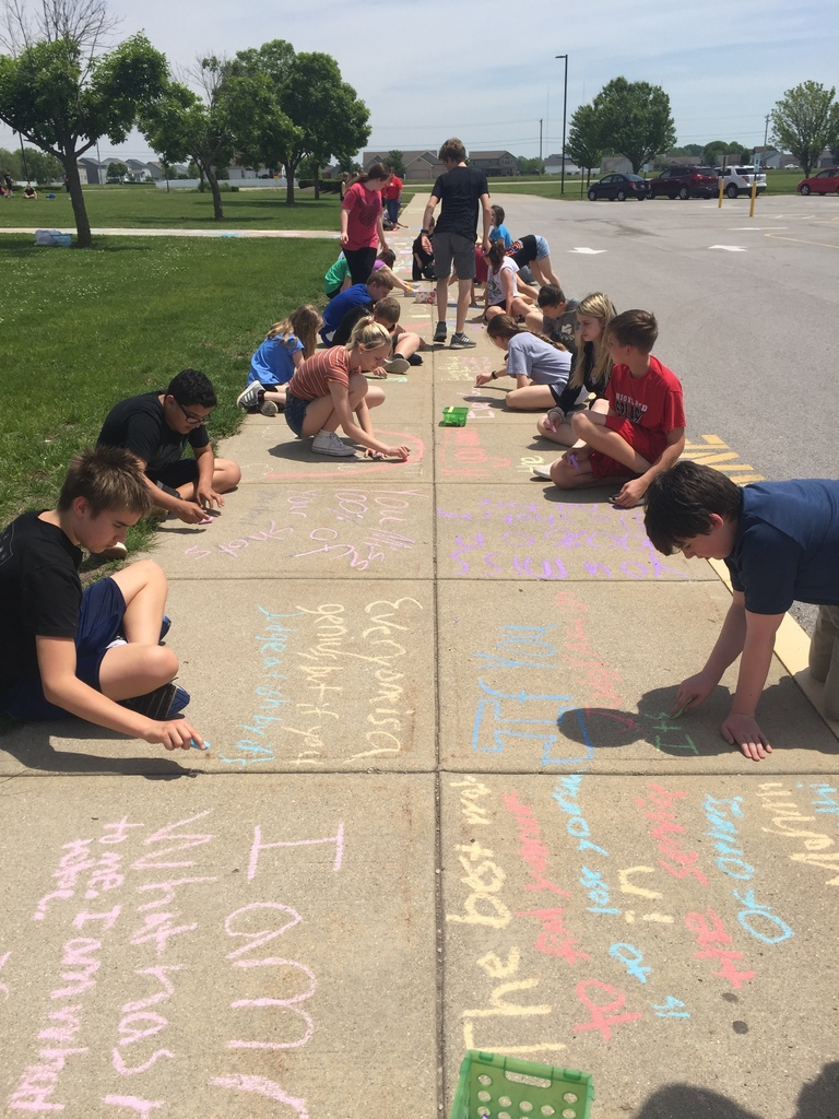 7 Red students celebrating 4th Quarter Great Page Challenge with water balloon toss and chalk art of favorite quotes from the year.